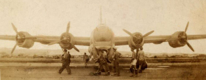 Head-on view of PB4Y-2 Privateer with airmen walking in front